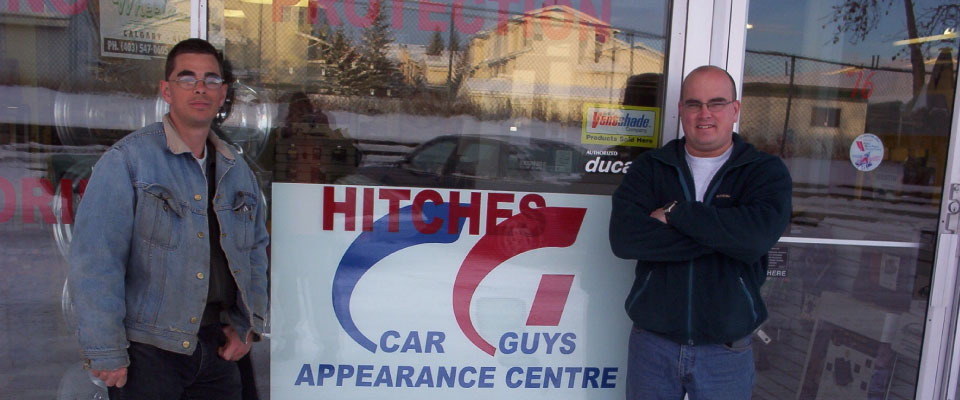 Car Guys in Front of Hitch Sign